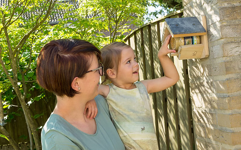 A young girl adding peanut butter to a Wexford Slate Peanut Butter Feeder